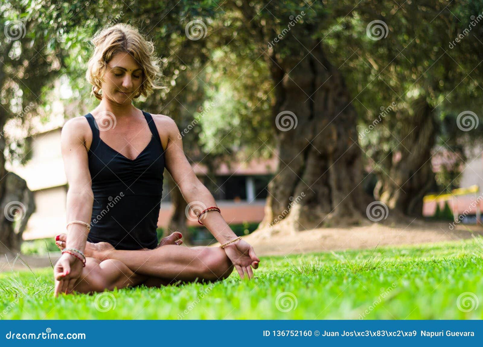 Yoga méditant et de pratique de femme, Padmasana Méditation sur Sunny Autumn Day At Park Séance d entraînement extérieure