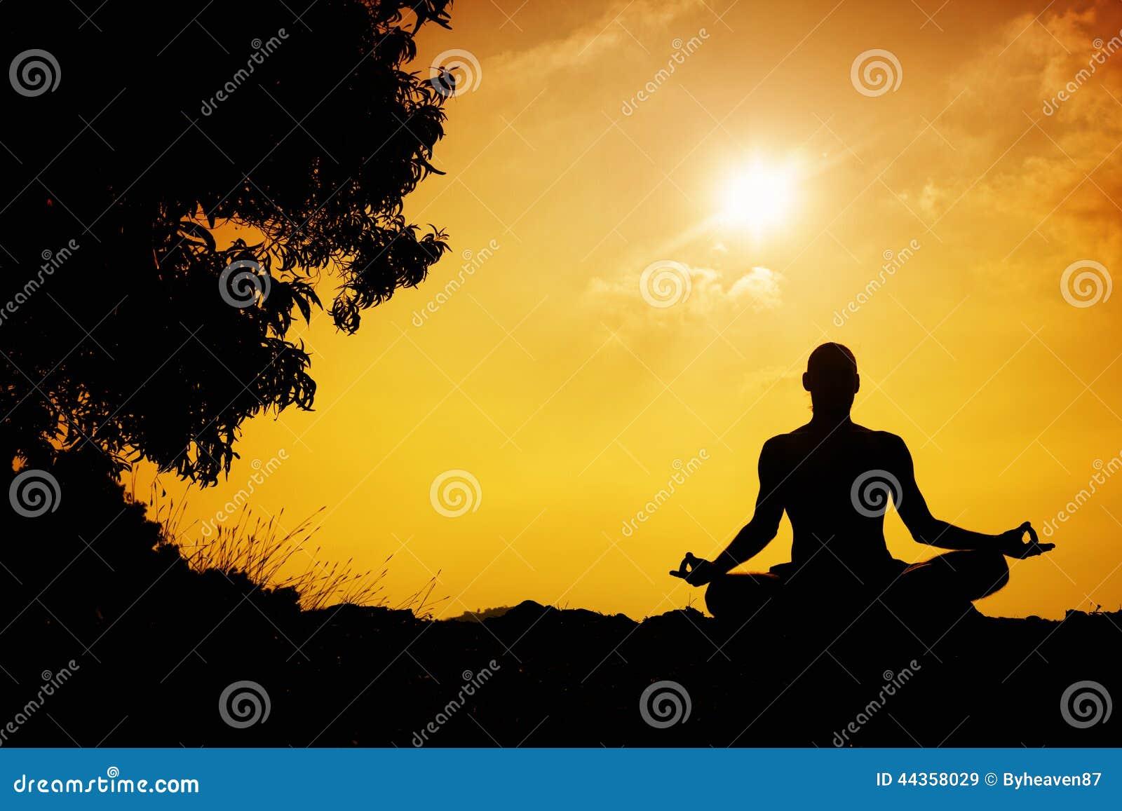Man silhouette in Yoga meditation pose near the tree at sunset in    Yoga Meditation Pose Silhouette