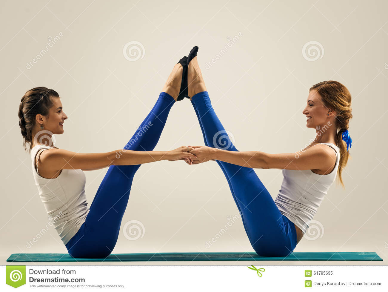 ... yogi sisters doing fitness training. studio shot. pair, couple yoga