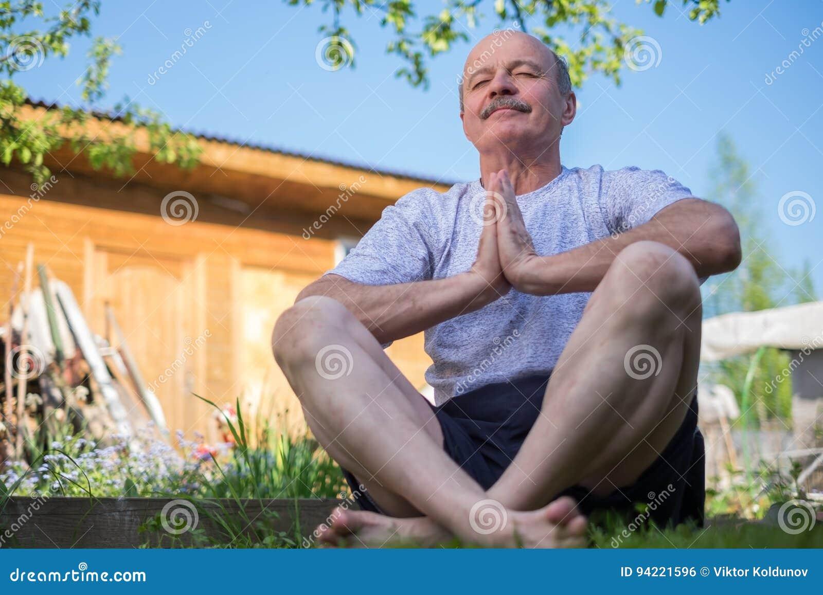 Yoga am Park Älterer Mann mit dem Schnurrbart mit namaste Sitzen Konzept von Ruhe und von Meditation