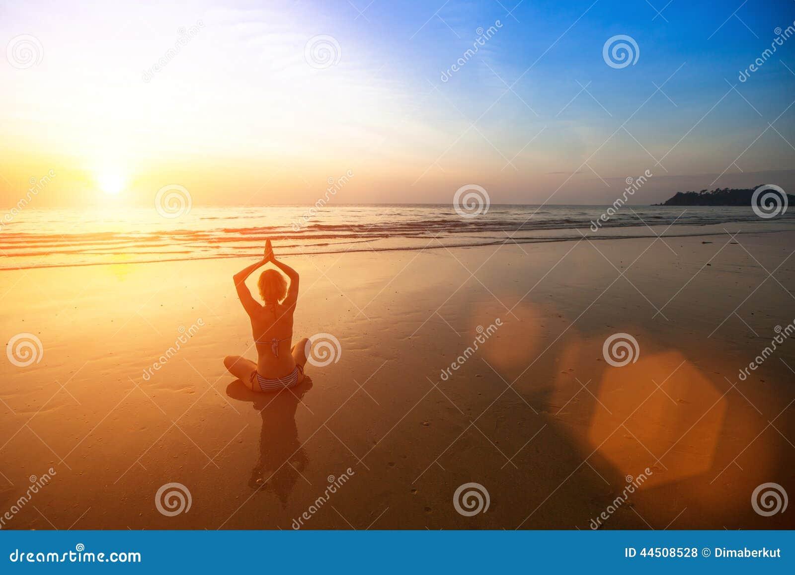Yoga practicante de la mujer en la playa del mar durante puesta del sol maravillosa