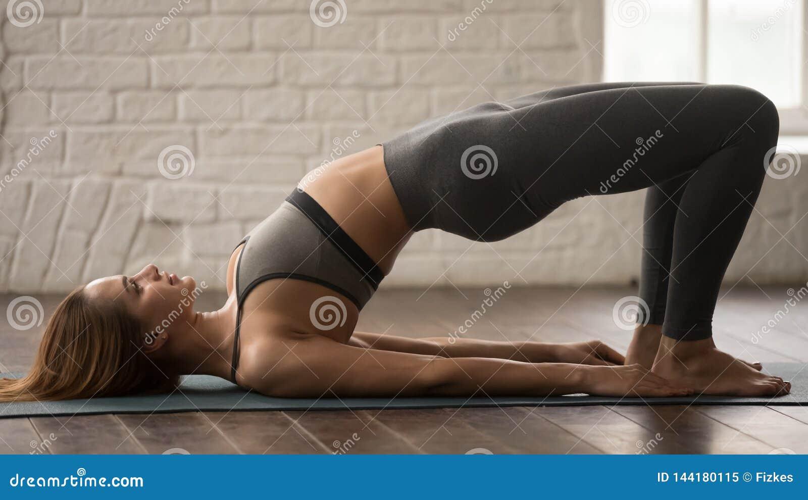 Yoga practicante de la mujer, haciendo ejercicio del puente de Glute, pithasana del pada del dvi