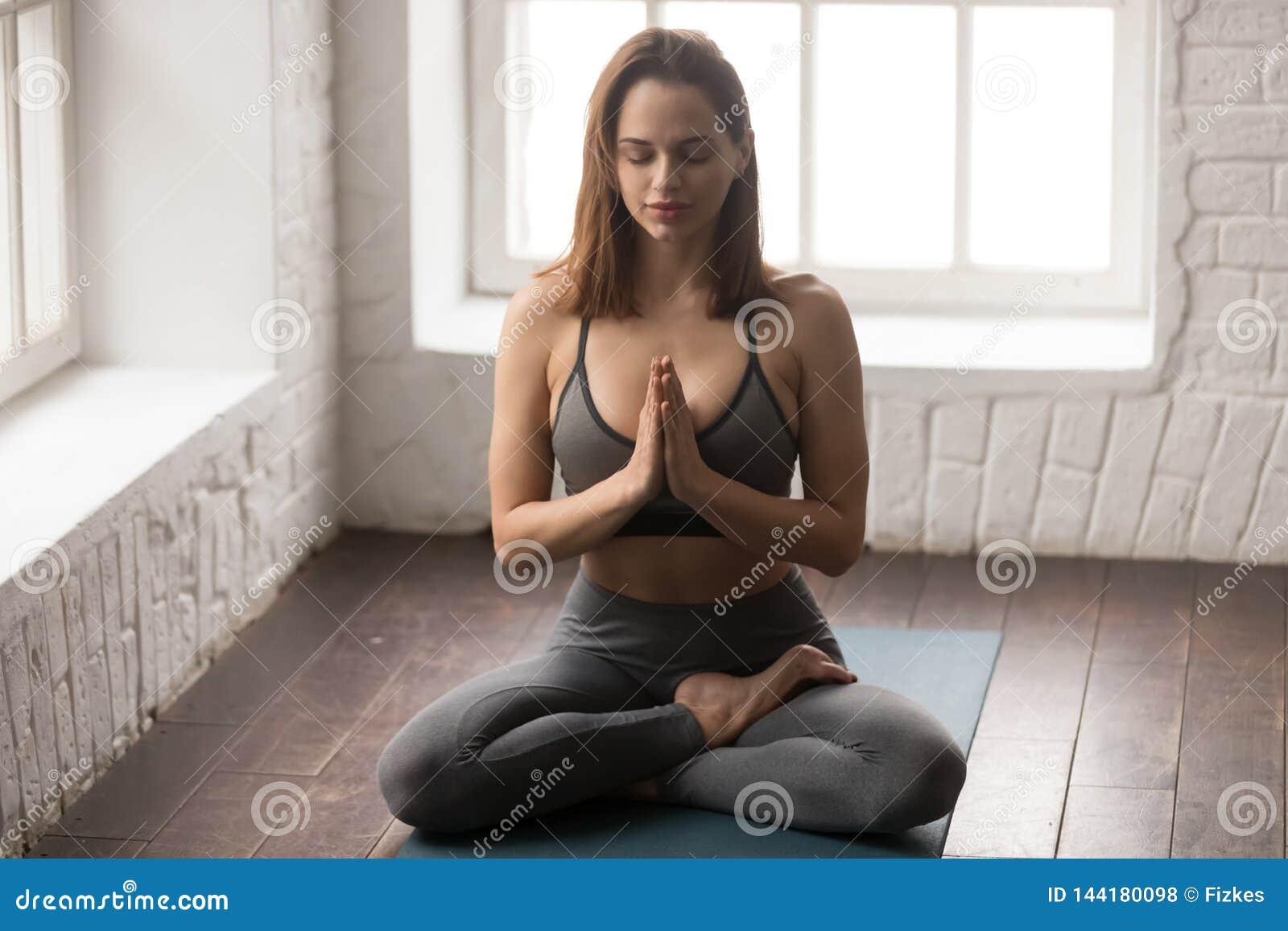 Yoga practicante de la mujer joven, sentándose en la actitud de Lotus, ejercicio de Padmasana