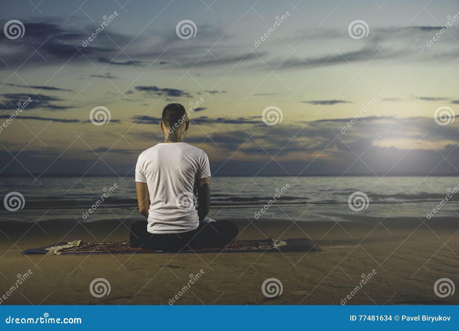 Yoga Practicante Del Hombre Joven Del Tatuaje En La Puesta Del Sol