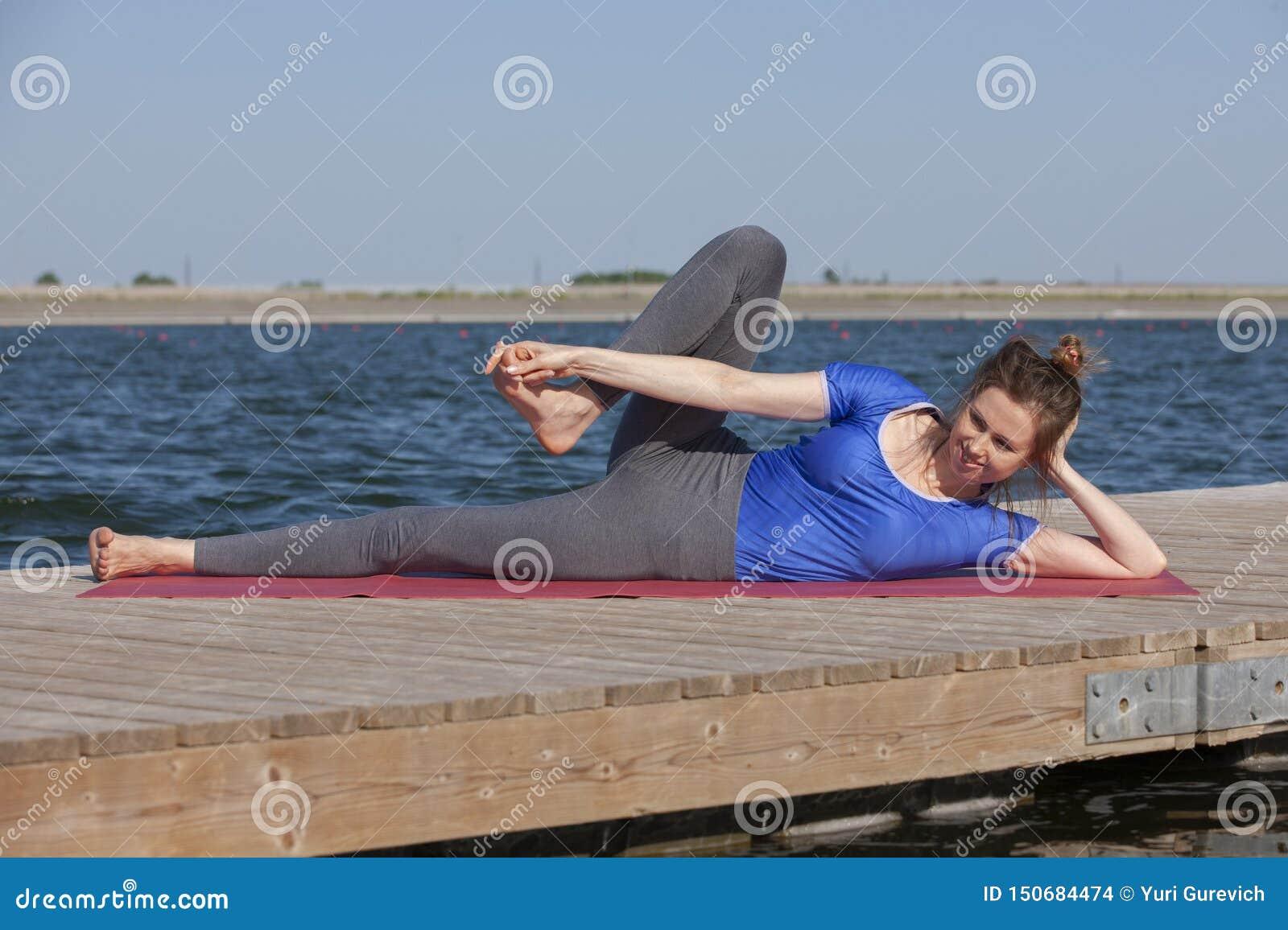 Yoga practicante hermosa de la mujer joven al aire libre por mañana