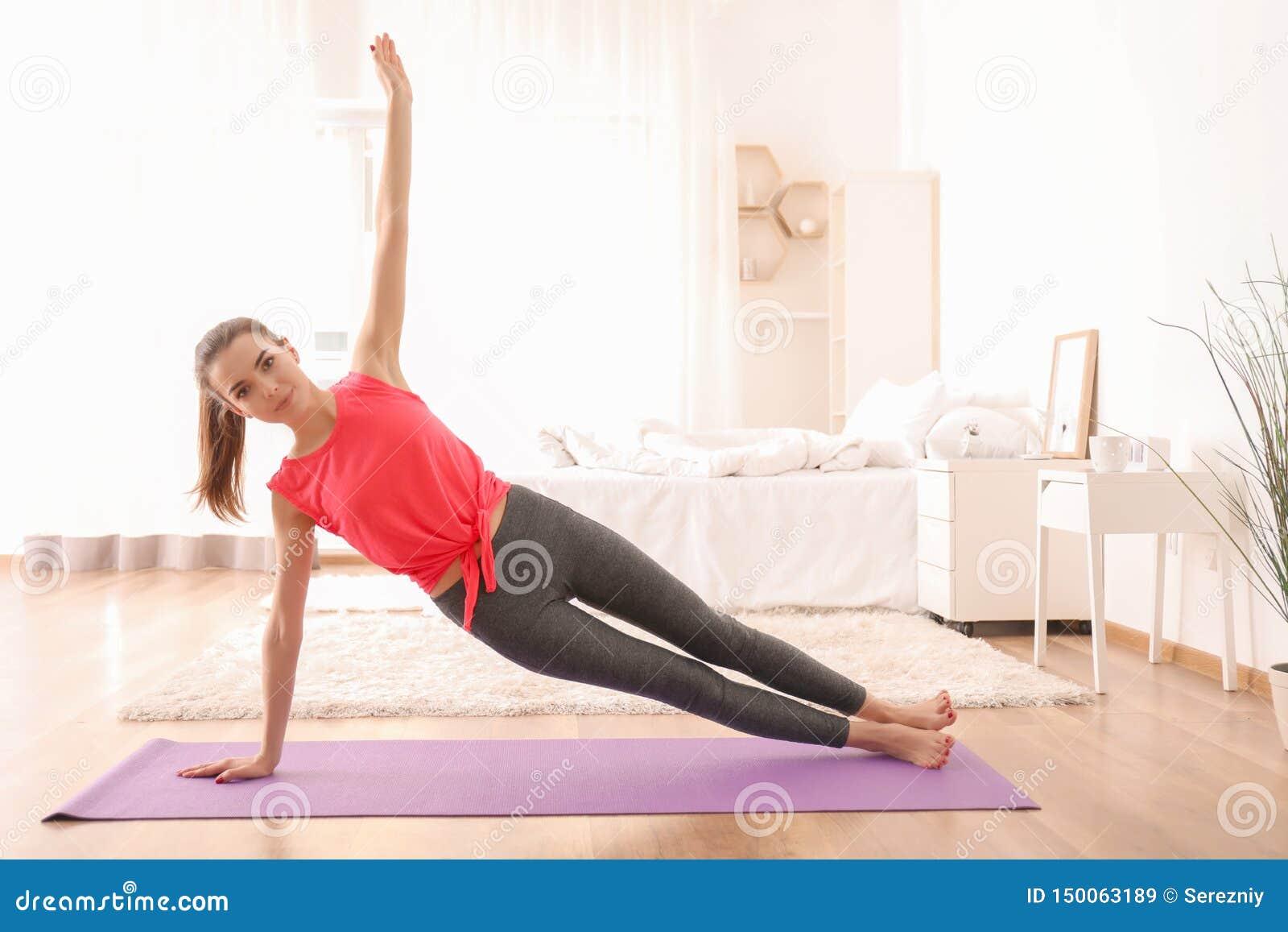 Yoga practicante hermosa de la mujer joven por mañana