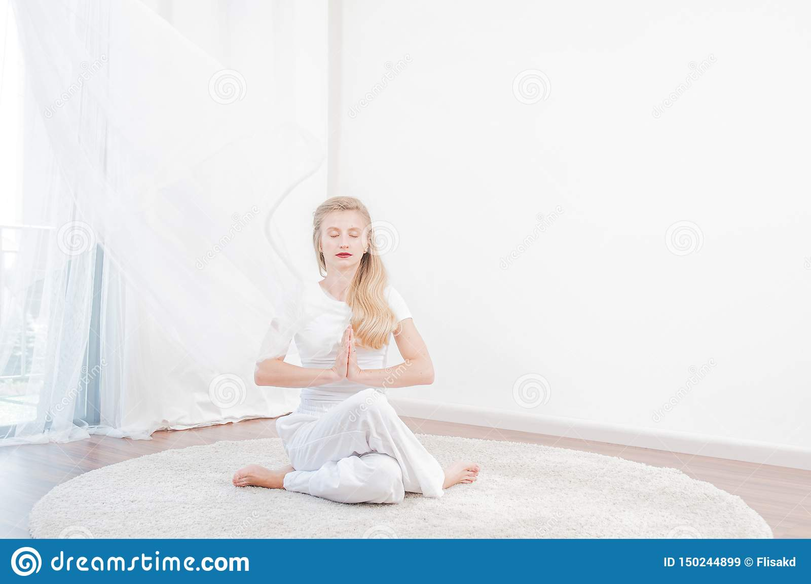 Beautiful woman is practicing yoga at home, girl doing Gomukasana exercise, sitting in Cow Face pose