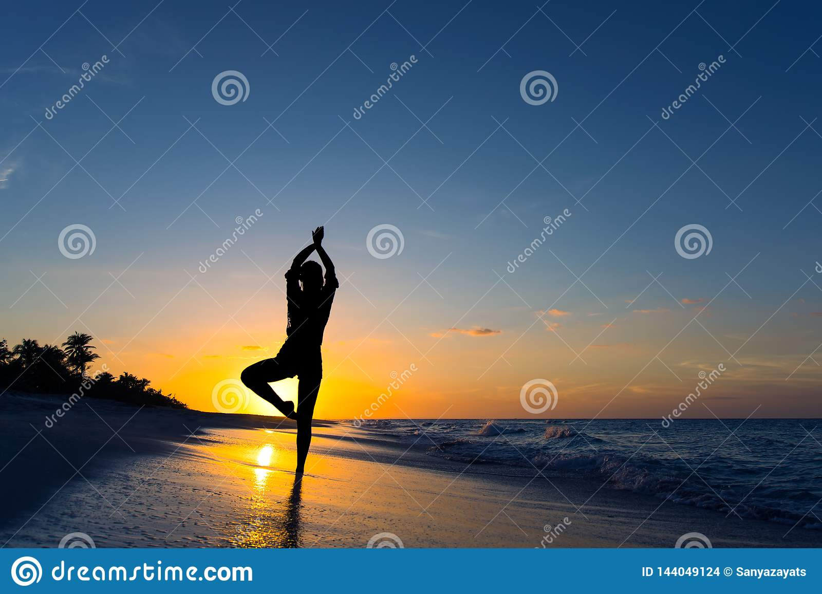 Yoga vrikshasana tree pose by woman in silhouette on the beach with sunset sky background. Free space for text.