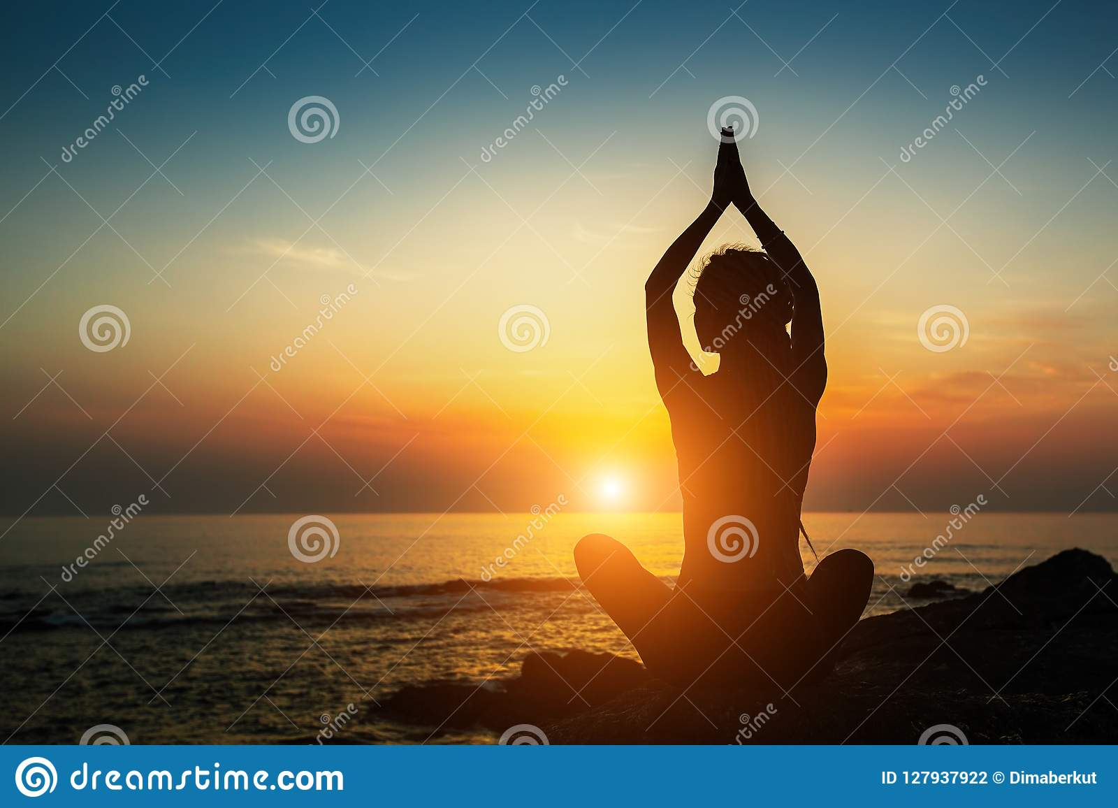 Yoga woman silhouette. Meditation on the ocean. Relax.