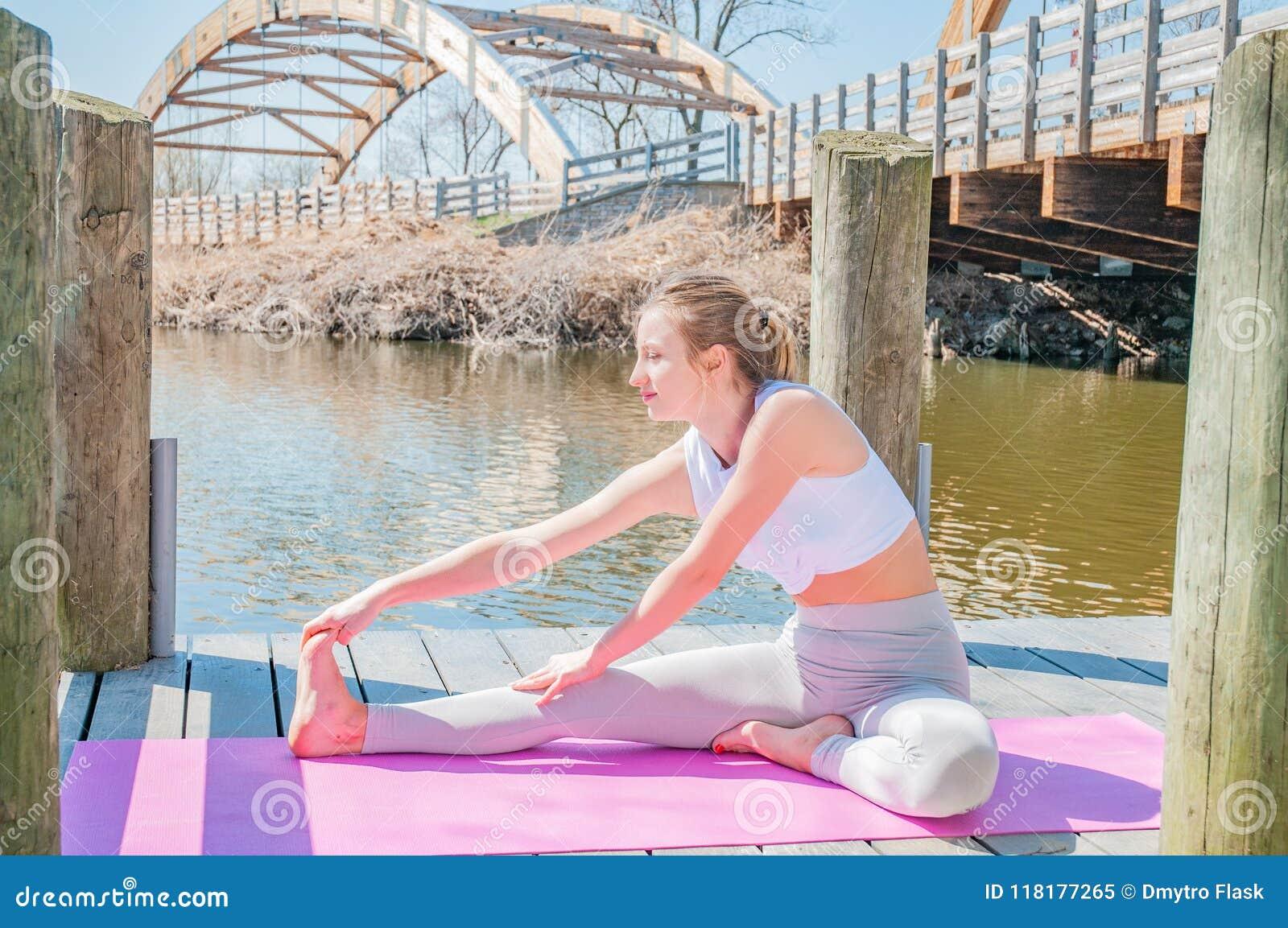 Yoga. Young woman practicing yoga Janu Sirsasana pose.