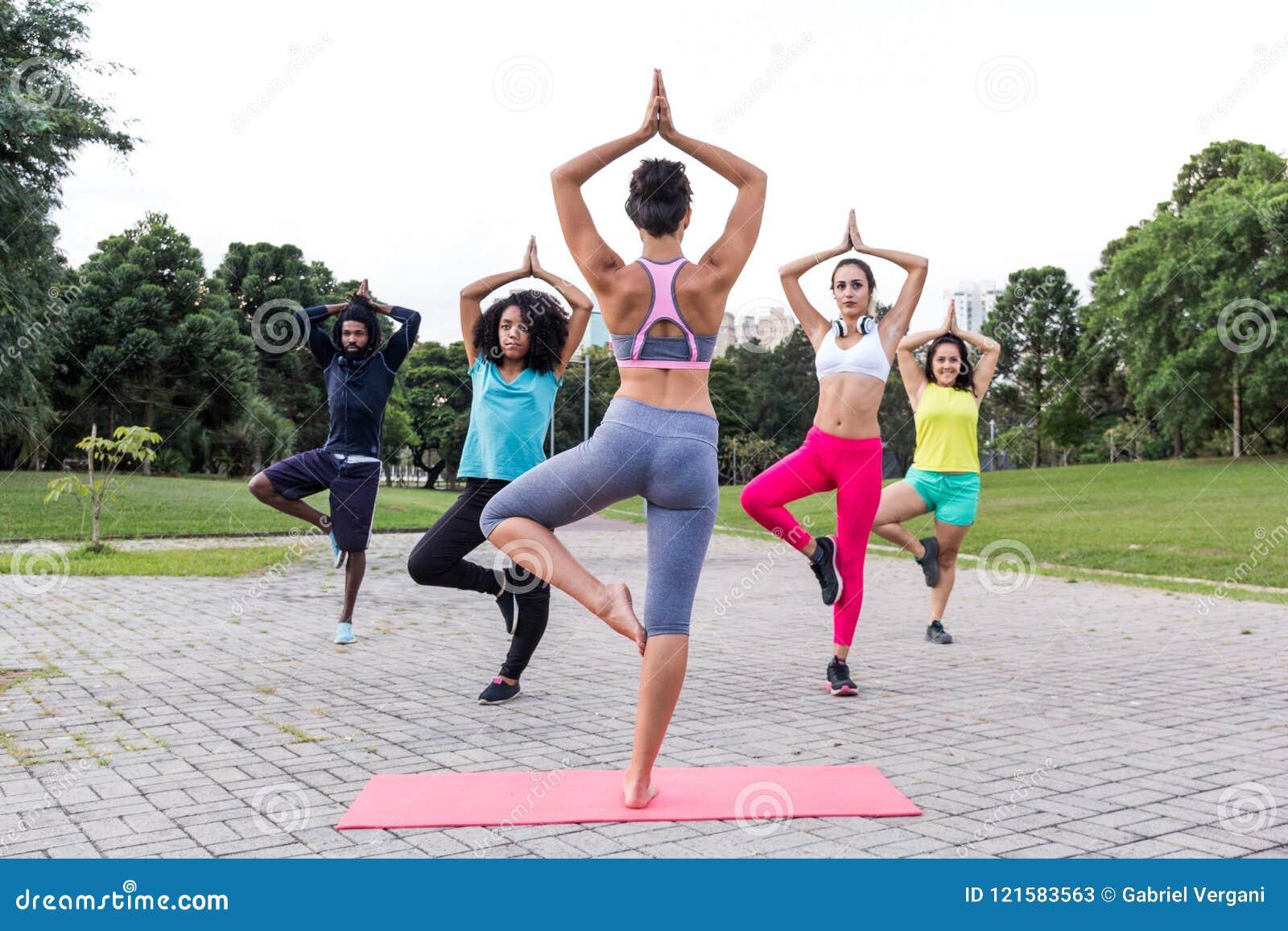 Yogaklassen in openlucht met multiraciale groep in verschillende physic