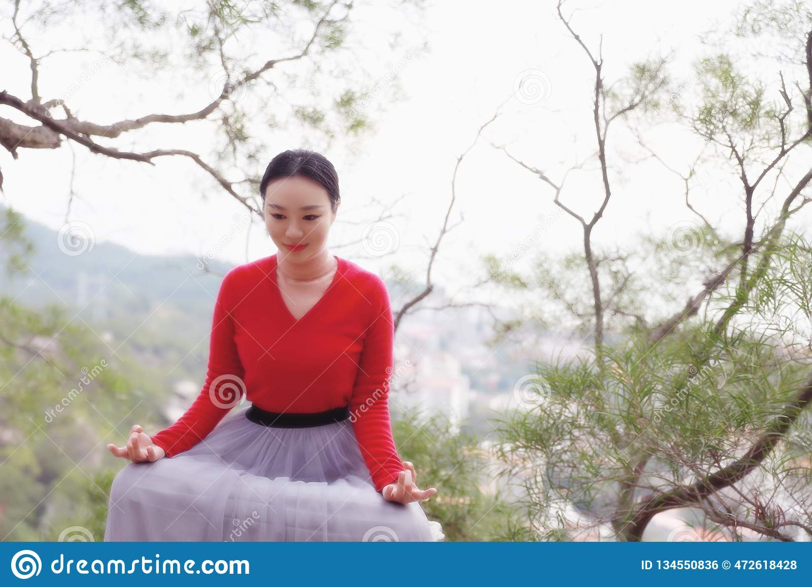 Yogakvinnan sitter i meditation poserar på bergmaximum vaggar