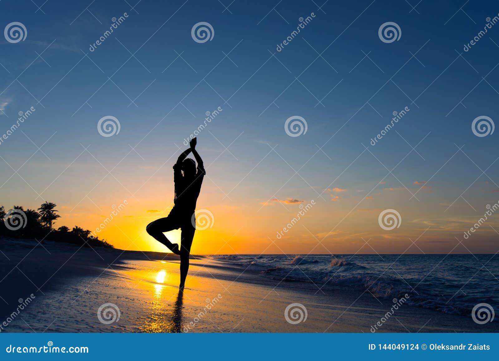 Yogavrikshasanaträdet poserar vid kvinnan i kontur på stranden med solnedgånghimmelbakgrund Fritt avstånd för text