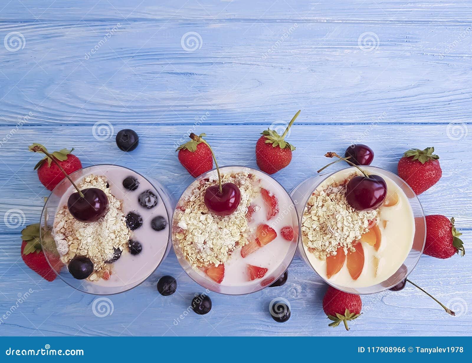 Yoghurt, van de de aardbei eigengemaakte zuivel heerlijke verfrissing van de havermeelbosbes de abrikozenkers op een blauwe houte