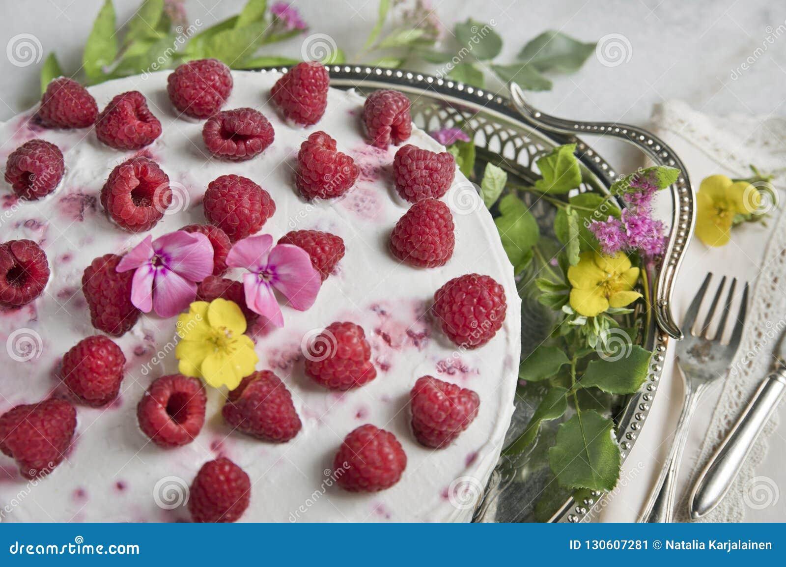 Yoghurtkaka med hallon på ett gammalt magasin med blommor, den gamla gaffeln och kniven