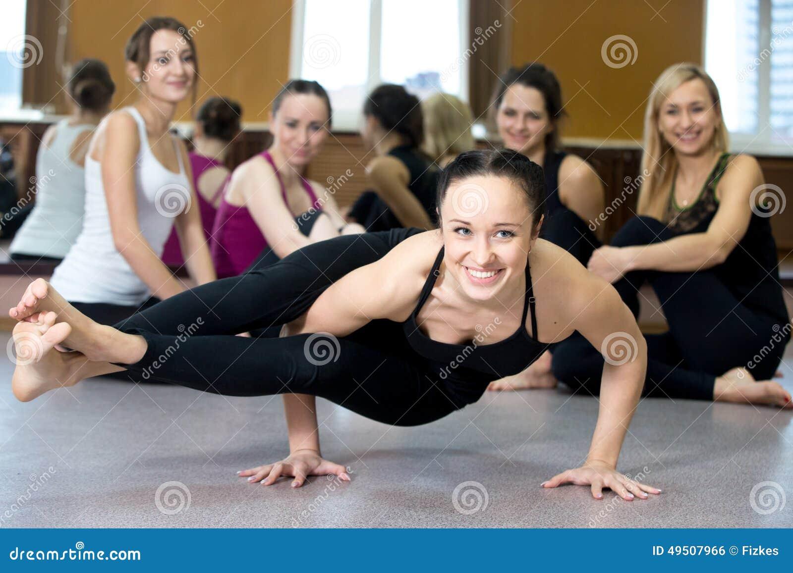 Yogi girl exercising, doing ashtavakrasana, handstand push-ups