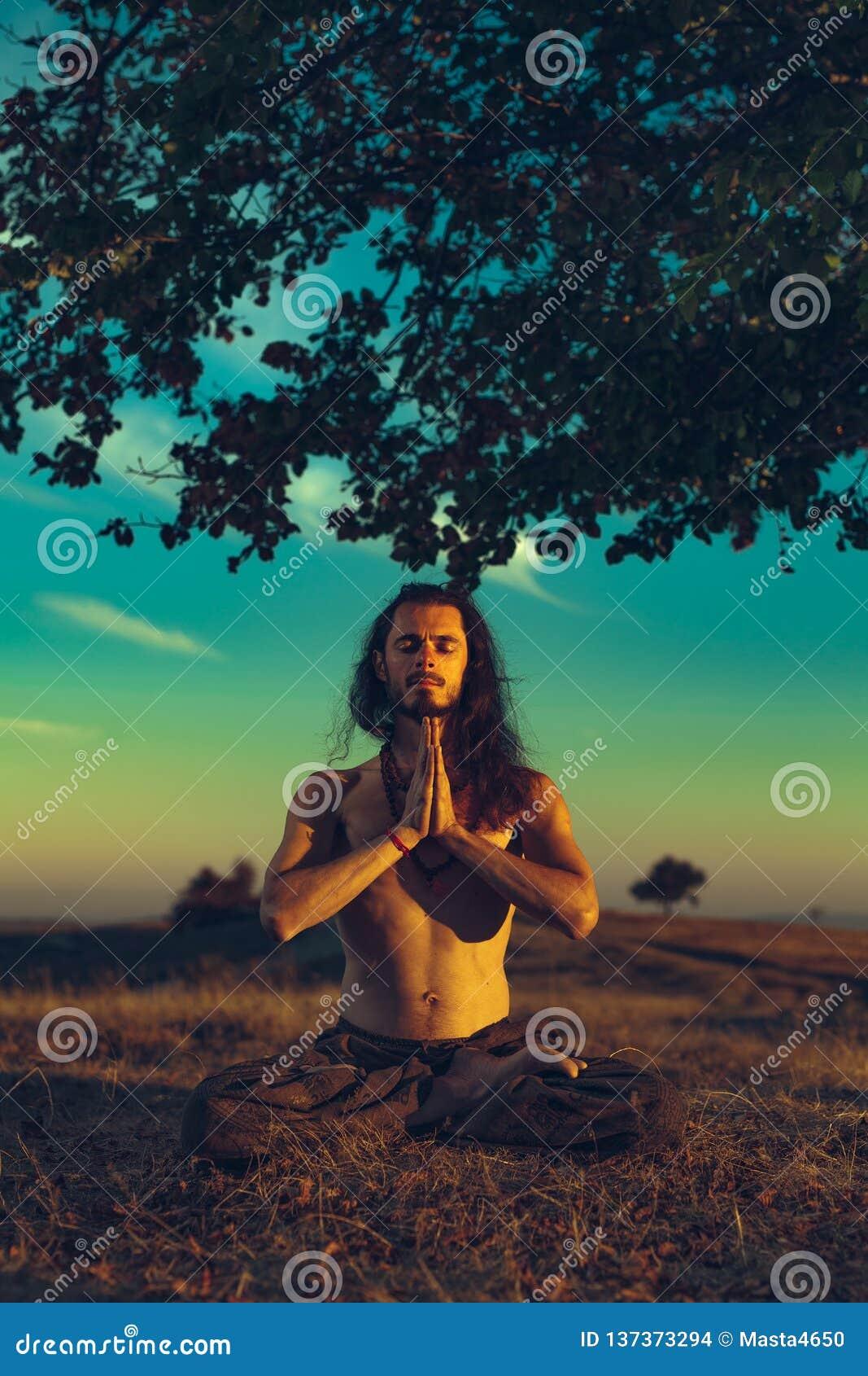 Yogiman som mediterar på solnedgången på kullarna Harmoni för andlighet för begrepp för livsstilavkoppling emotionell med naturen