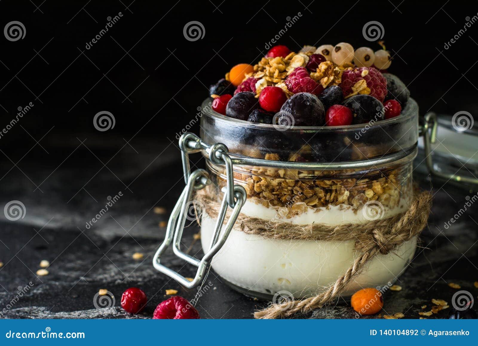 Yogur con el granola y las bayas en pequeño tarro, fresas, arándanos , grosella negra dulzor Yogur hecho en casa Alimento sano