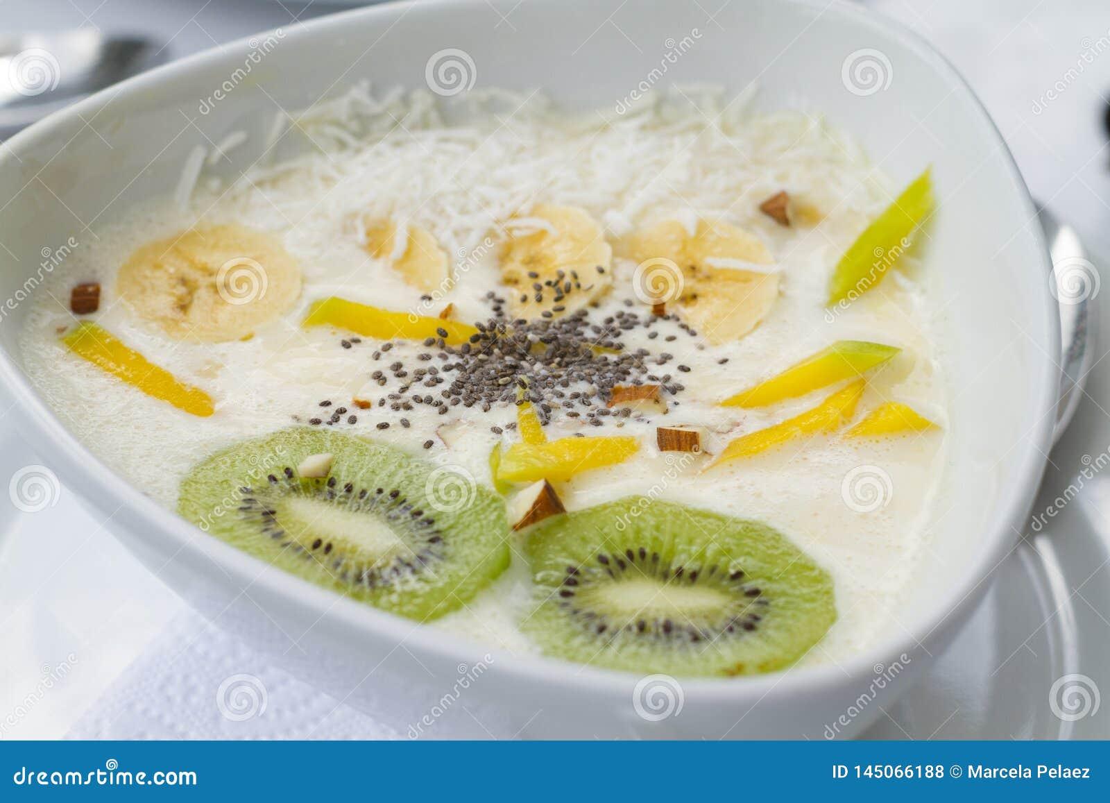 Yogur con el kiwi del chia del mango en el plato de cerámica blanco con los manteles blancos