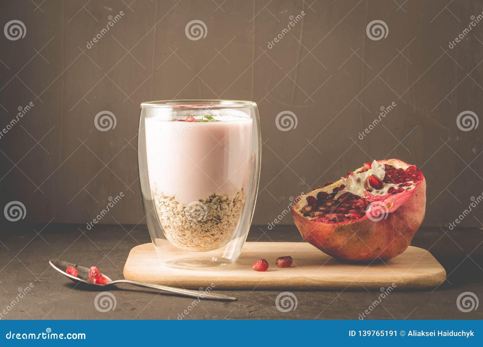 Yogur Yogur con los cereales, el granate y la menta en vidrio y fruta de la granada en una bandeja de madera Tabla oscura del bac