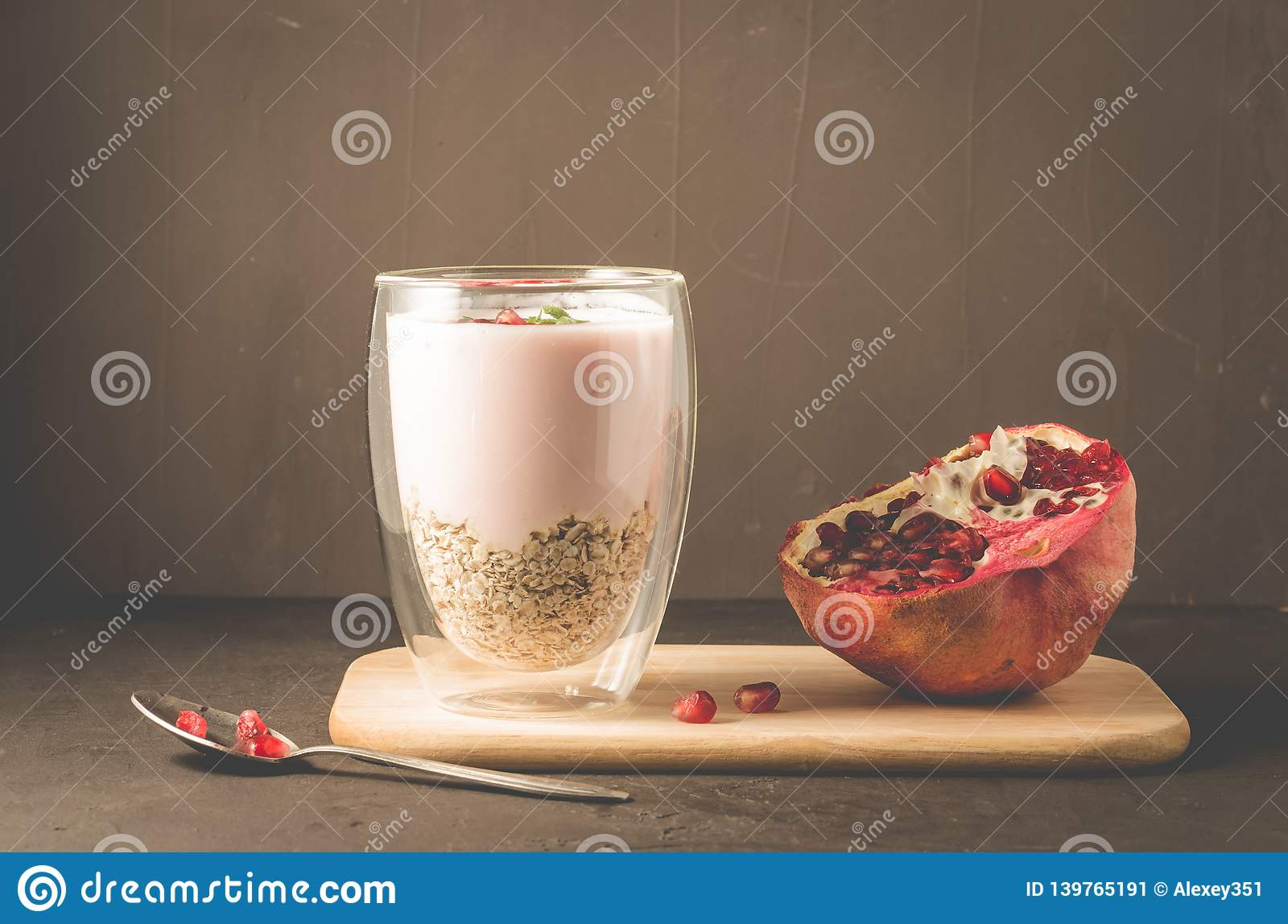 Yogurt. Yogurt with cereals, garnet and mint in glass and pomegranate fruit on a wooden tray. Dark backgtound table. Selective