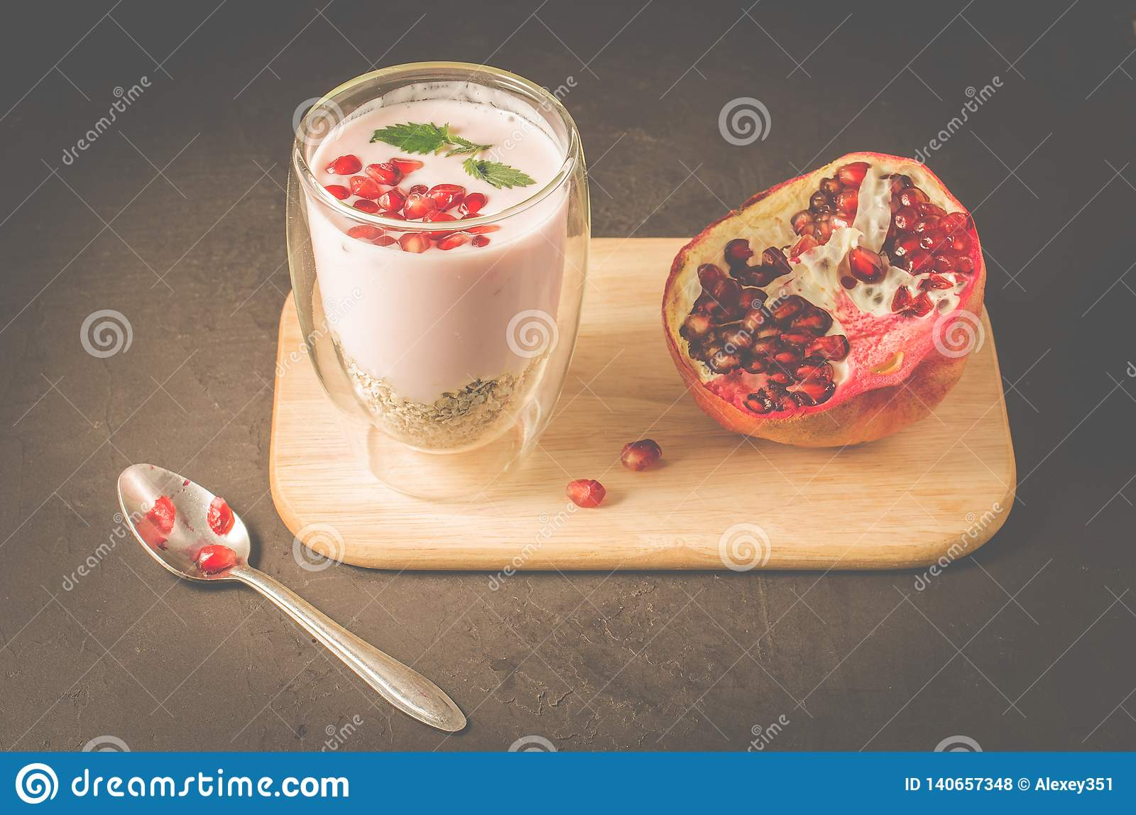 Yogurt. Yogurt with cereals, garnet and mint in glass and pomegranate fruit on a wooden tray. Dark backgtound table. Sweet dessert