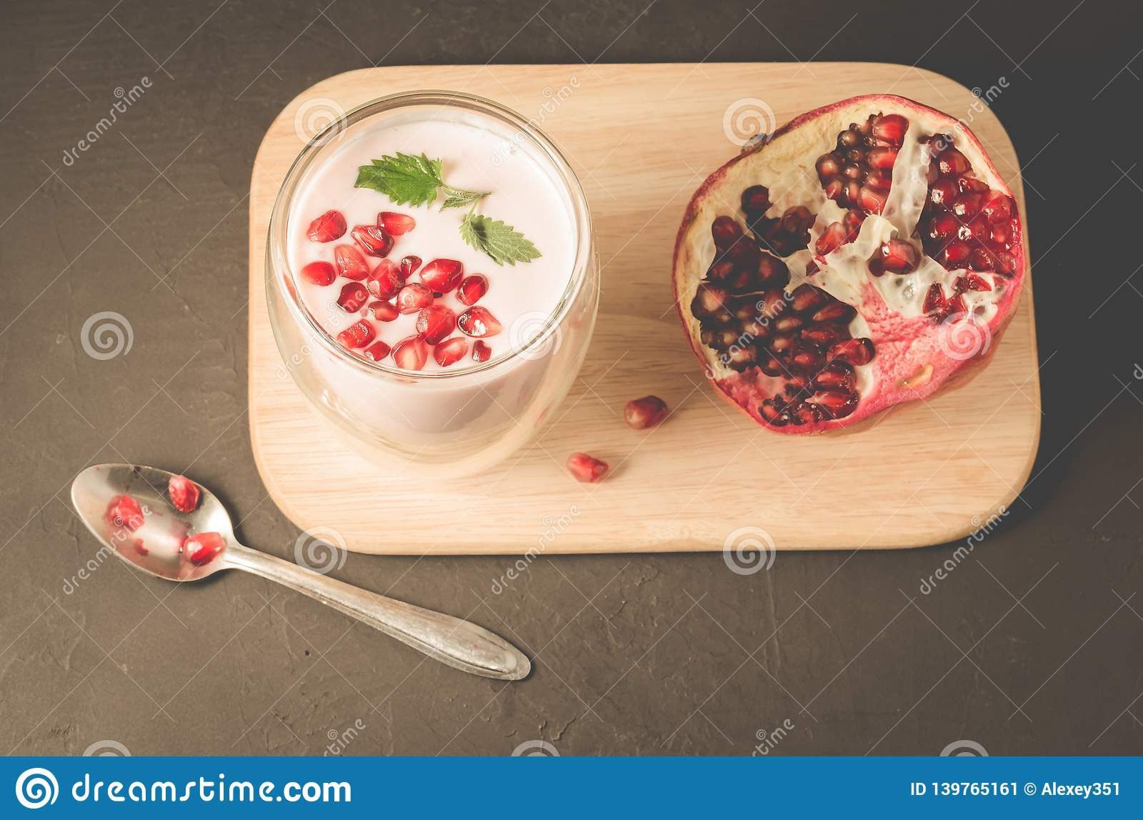 Yogurt. Yogurt with cereals, garnet and mint in glass and pomegranate fruit on a wooden tray. Dark backgtound table. Top view.