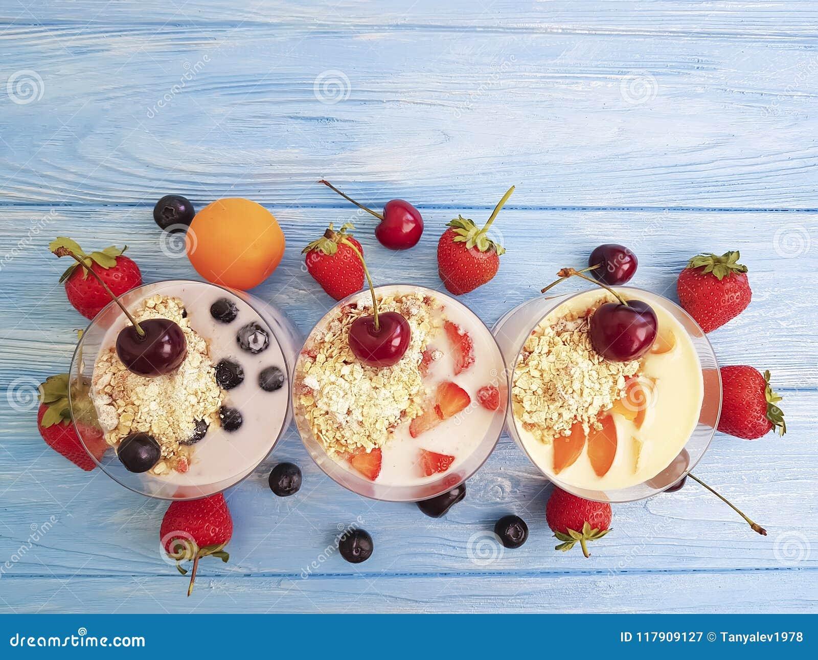 Yogurt, ciliegia deliziosa dell albicocca del rinfresco della latteria della fragola del mirtillo della farina d avena su un fond