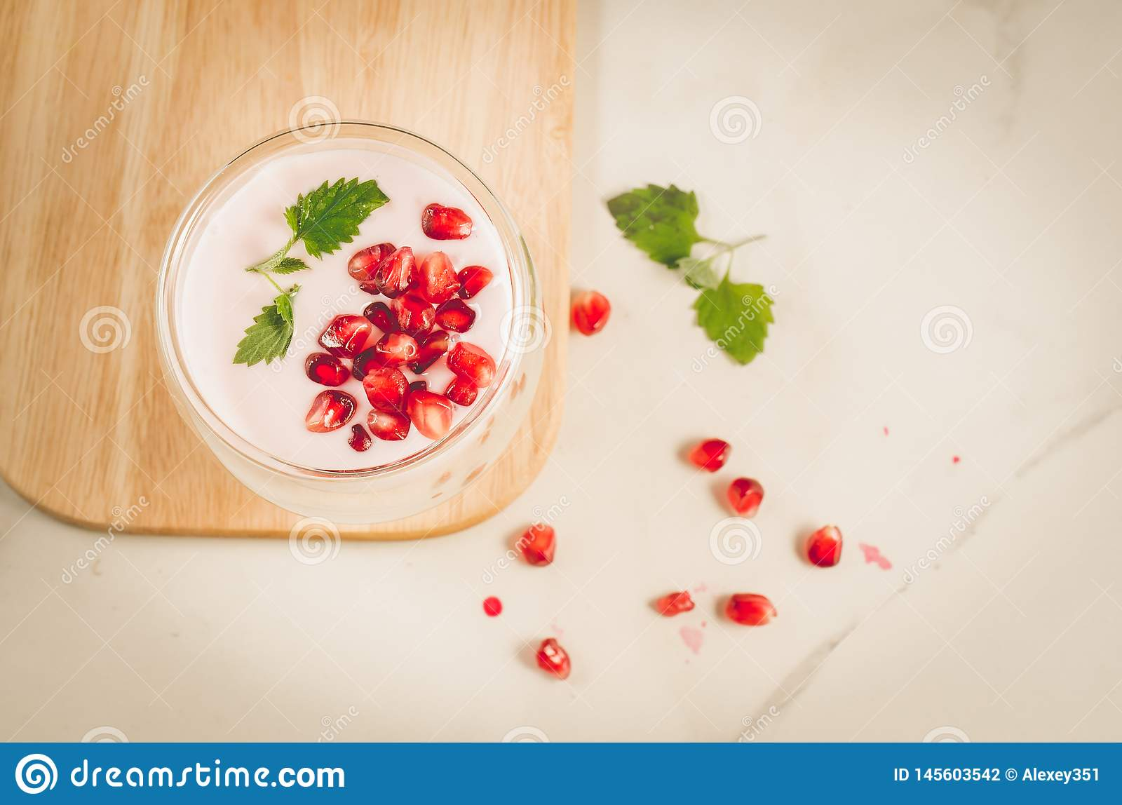 Yogurt. Yogurt with garnet and mint in glass on a wooden tray and the scattered pomegranate seeds on a white table. Top view.