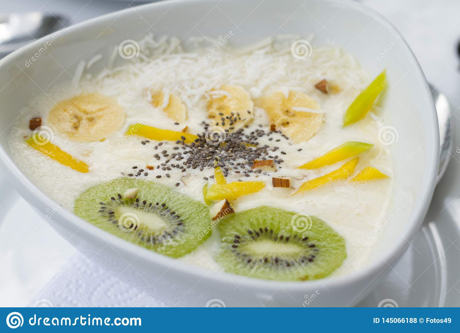 Yogurt with mango chia kiwi in white ceramic dish with white tablecloths