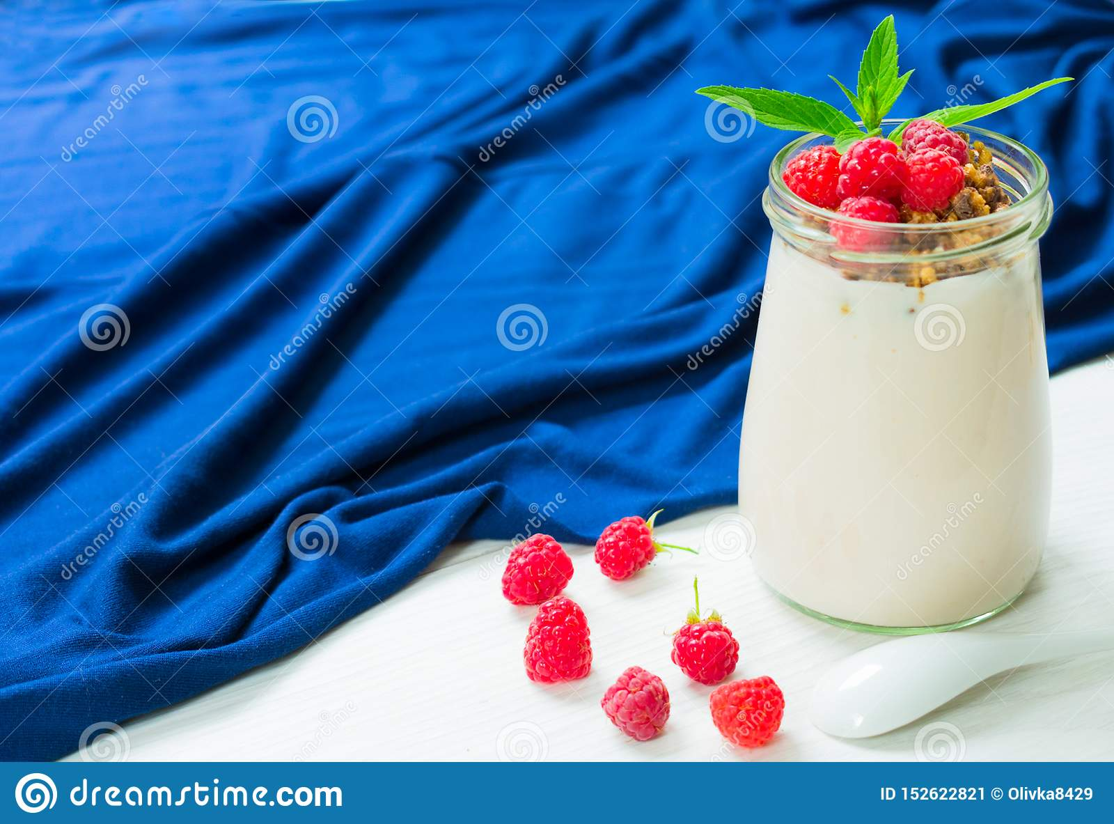Yogurt with raspberry berries and muesli, decorated with mint leaves, in a glass jar on a white table with a blue tablecloth