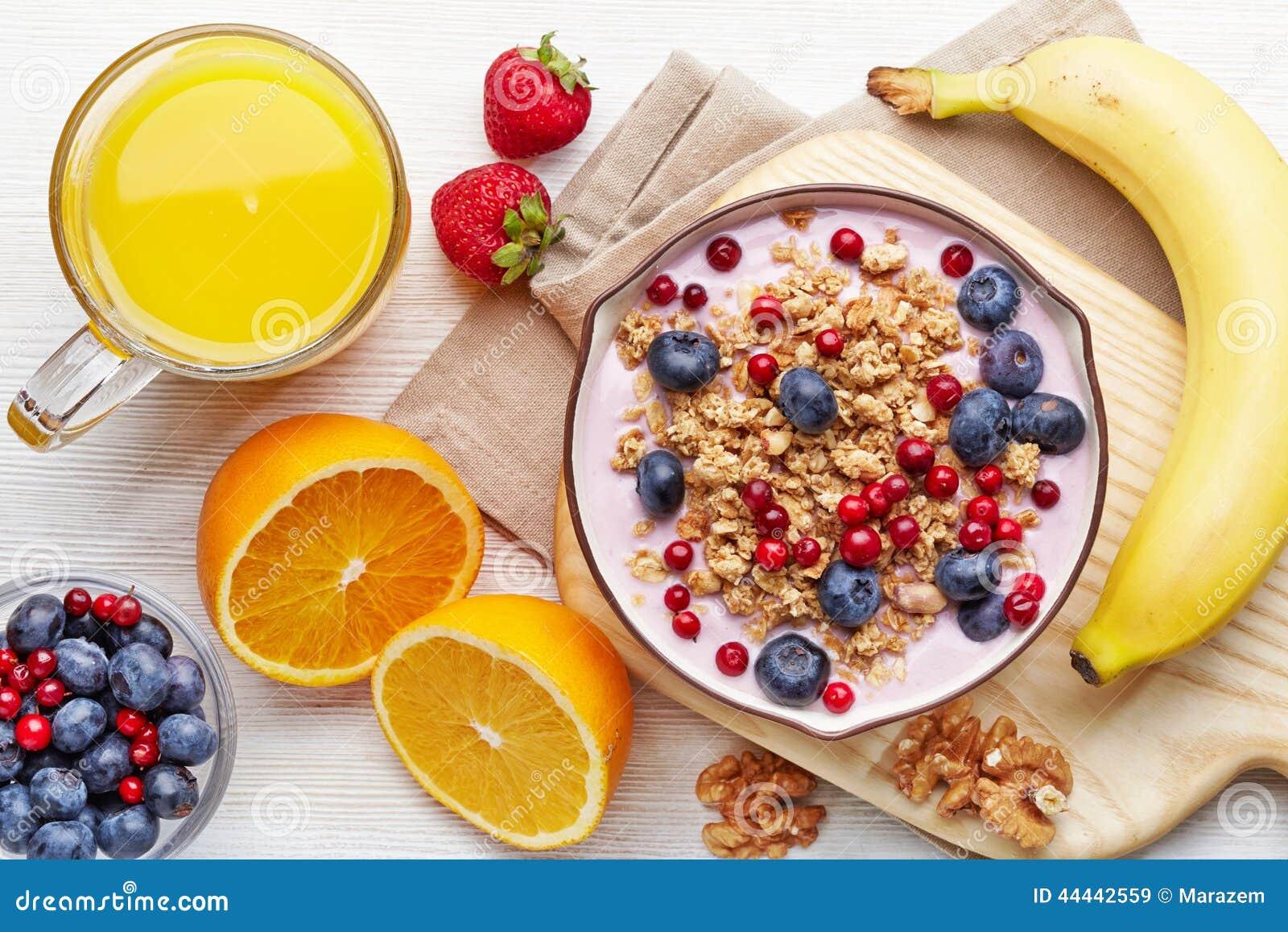 Yogurt sano della prima colazione con granola e le bacche