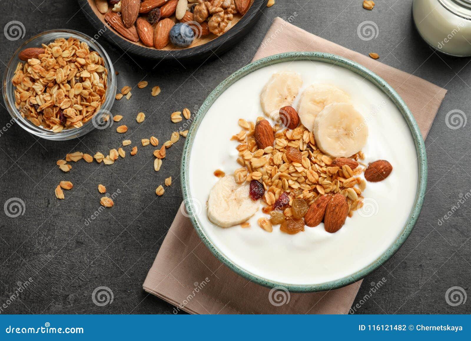 Yogurt saporito con la banana ed il granola per la prima colazione