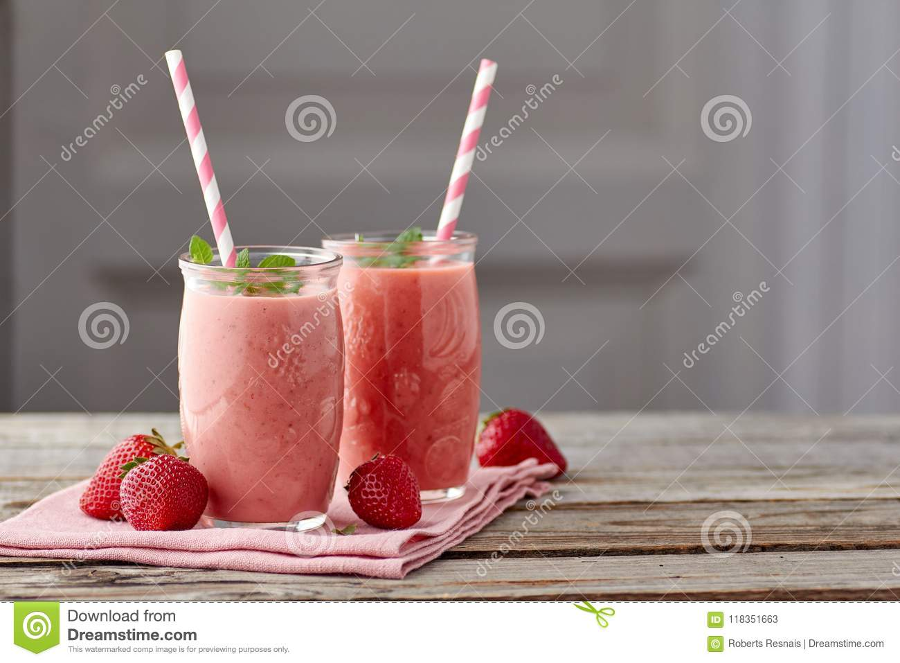 Yogurt and strawberry smoothie in two jars with drinking straw on wooden table