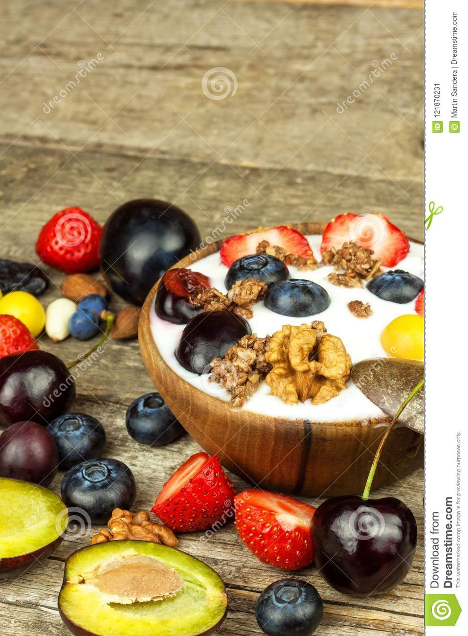 Yogurt with summer fruit on an old wooden table. Fruit refreshment. Snack for children.