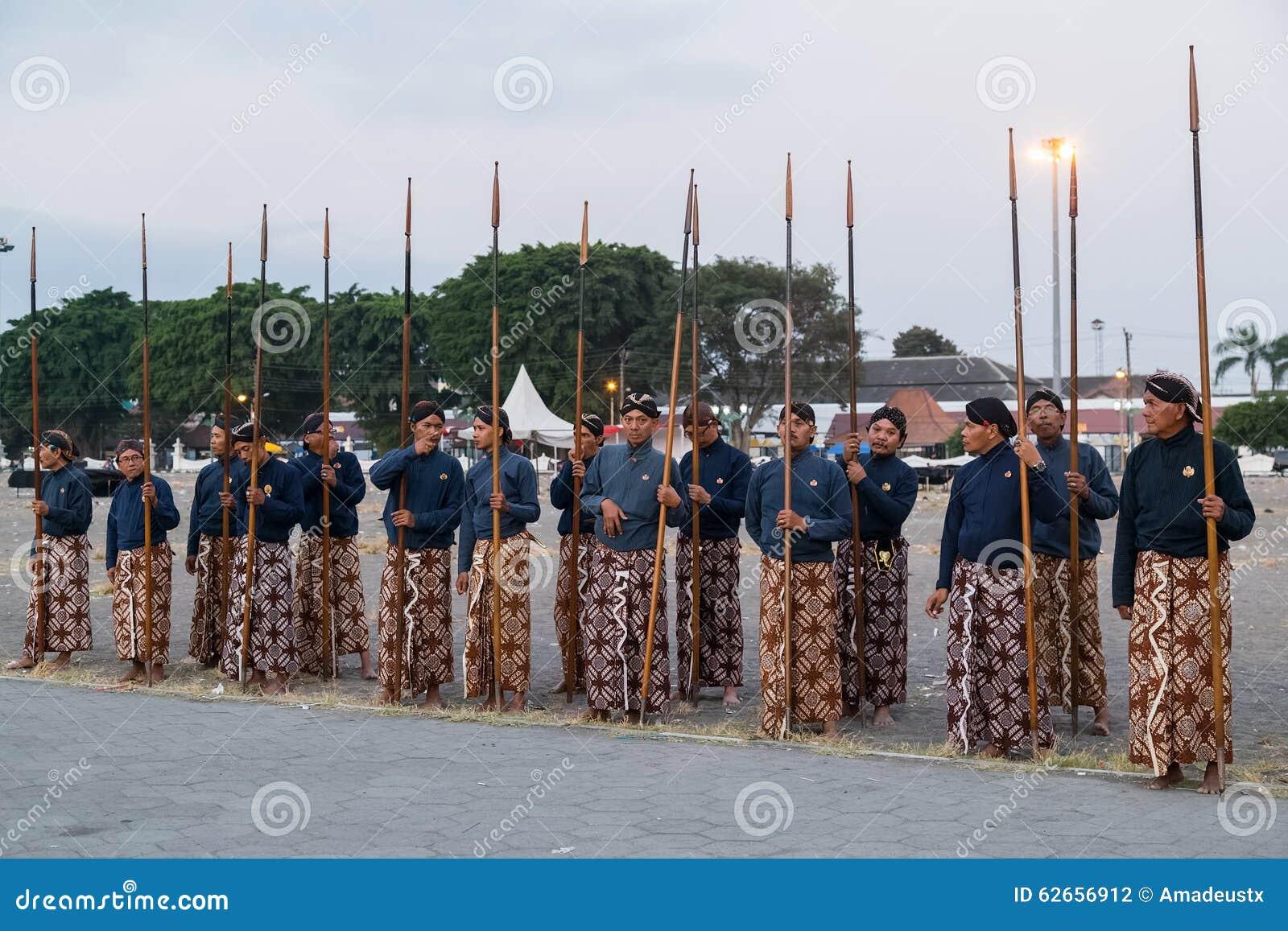 YOGYAKARTA, INDONESIEN - CIRCA IM SEPTEMBER 2015: Zeremonieller Sultan Guards in den Sarongs, die mit Stangen vor Sultan Palace s
