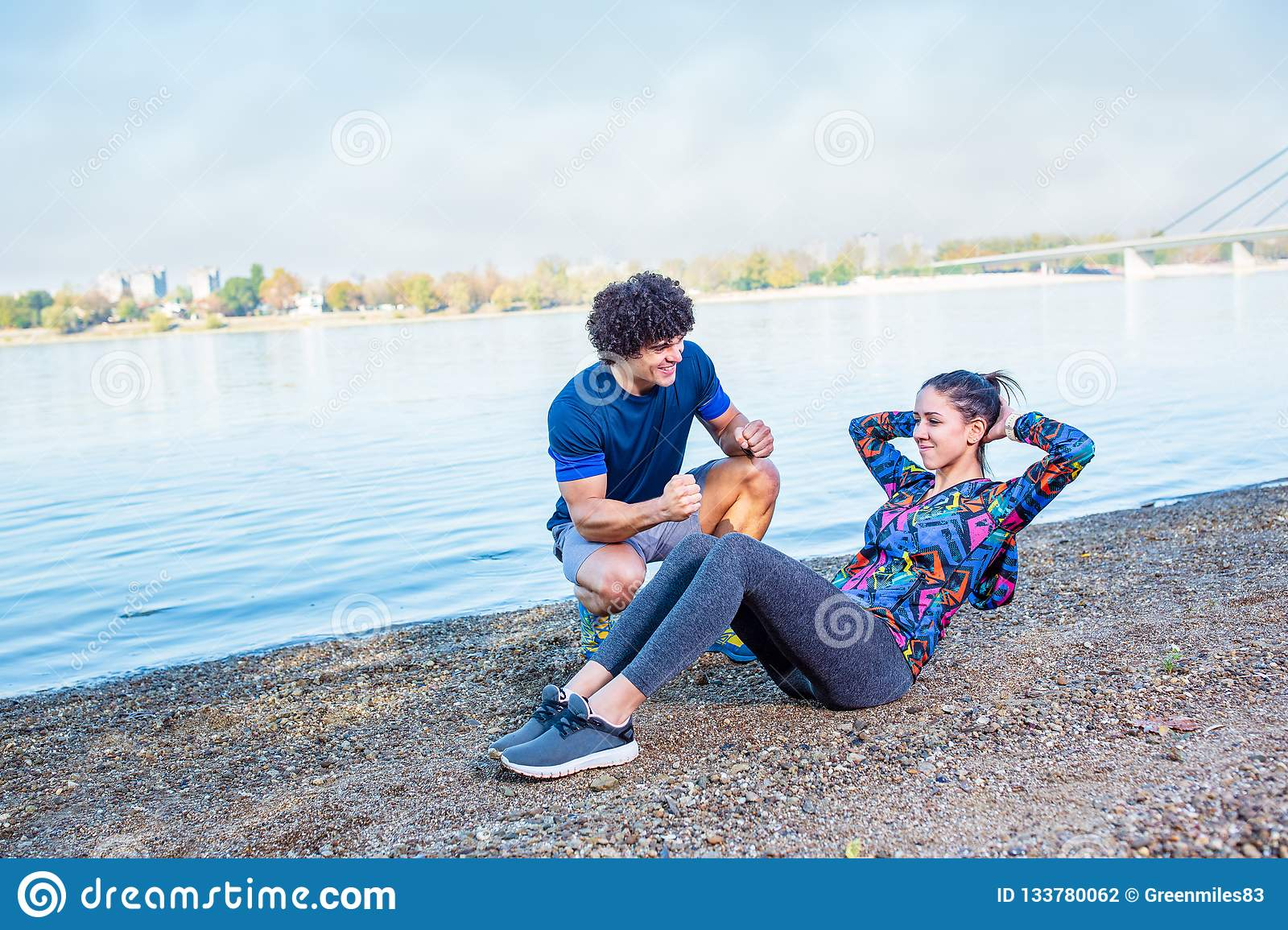 You can do it - fitness Trainer assisting young woman doing sit