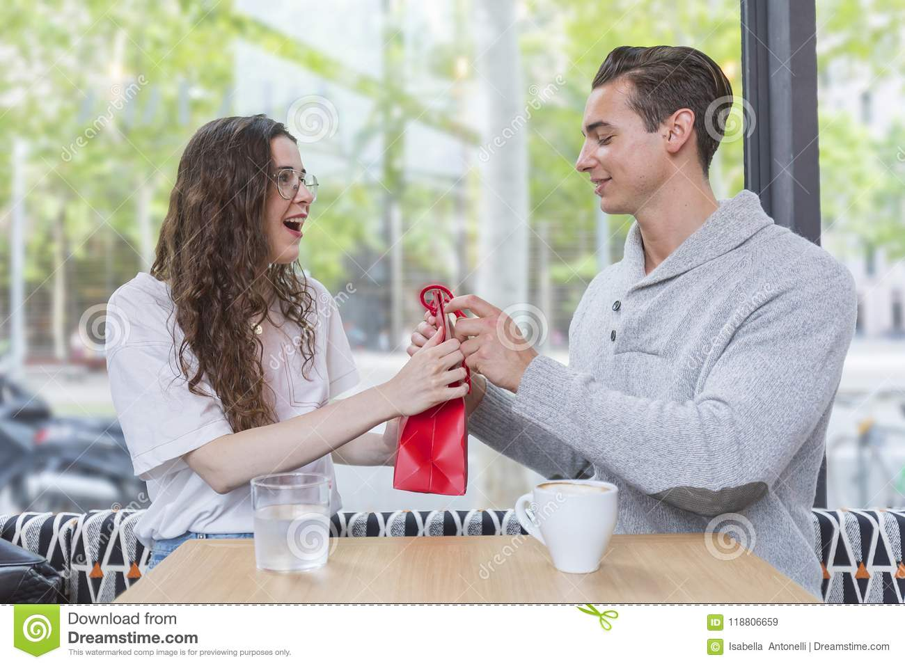 Happy young couple sitting at the cafe table with a present