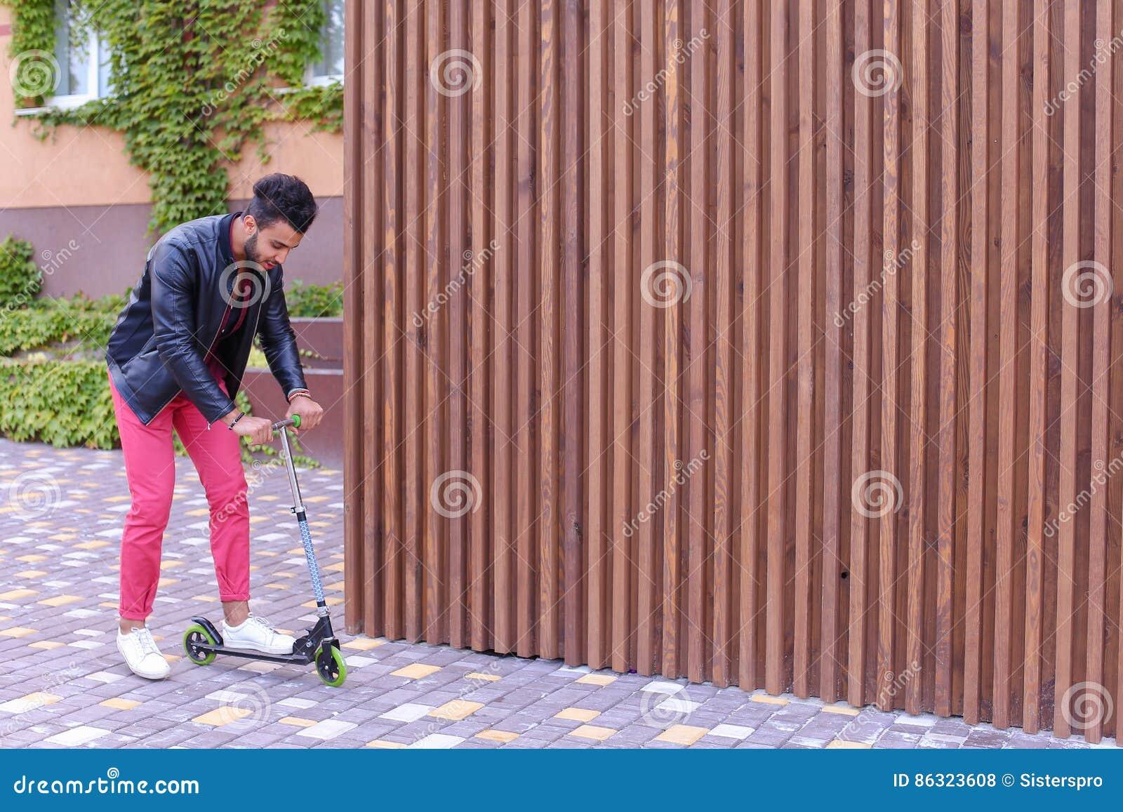 Yound maschile arabo affascinante Guy Rides Scooter, divertimento e