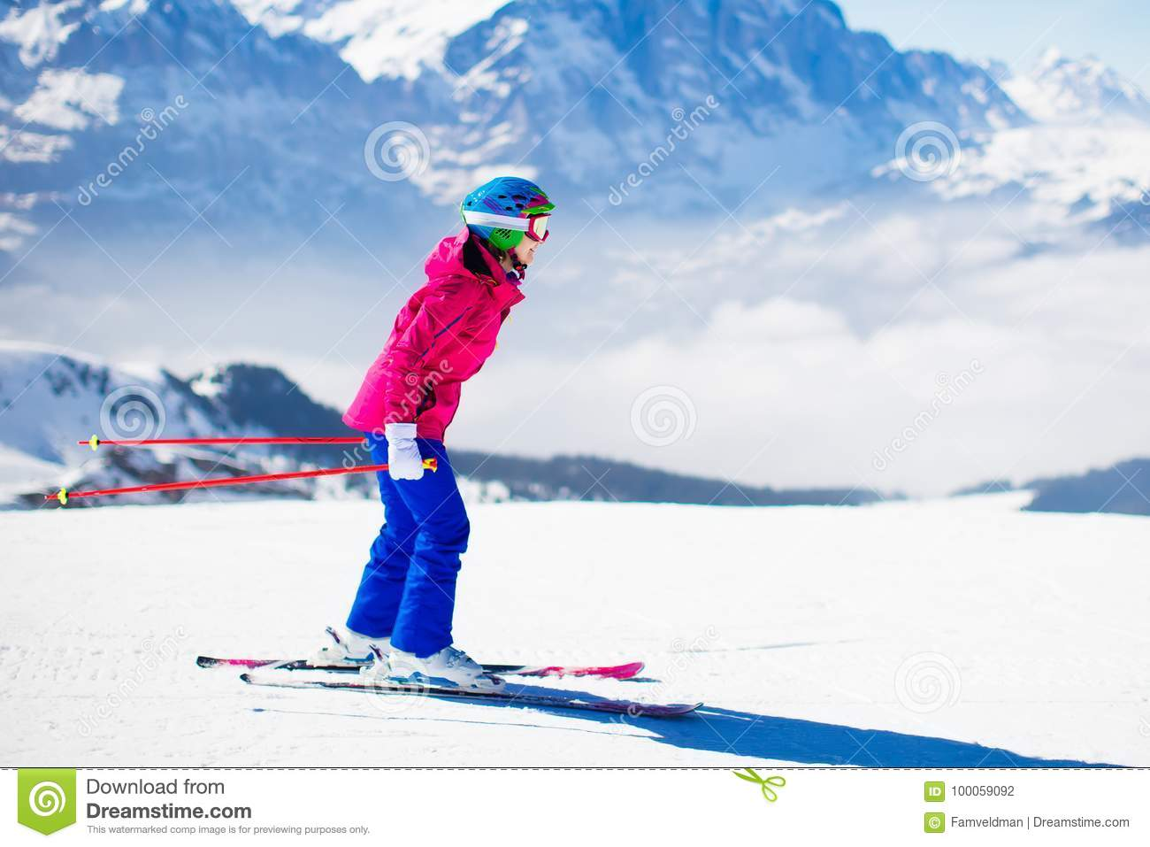 02a4e80c803 Young active woman skiing in mountains. Female skier kid with safety  helmet