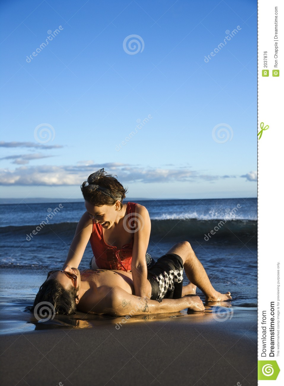 Young adult couple on beach.