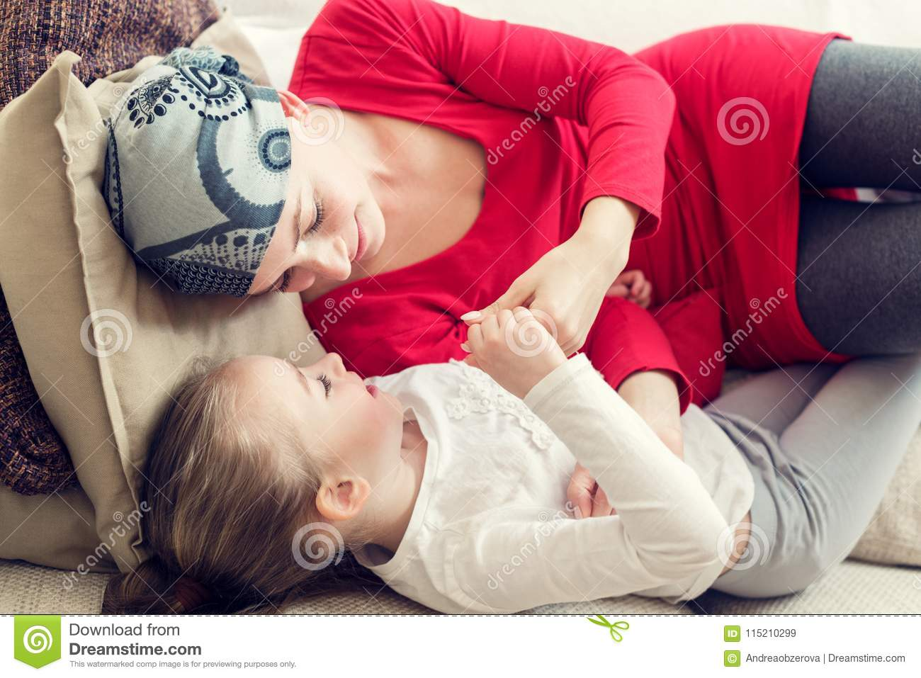 Young adult female cancer patient spending time with her daughter at home, relaxing on couch. Cancer and family support concept.