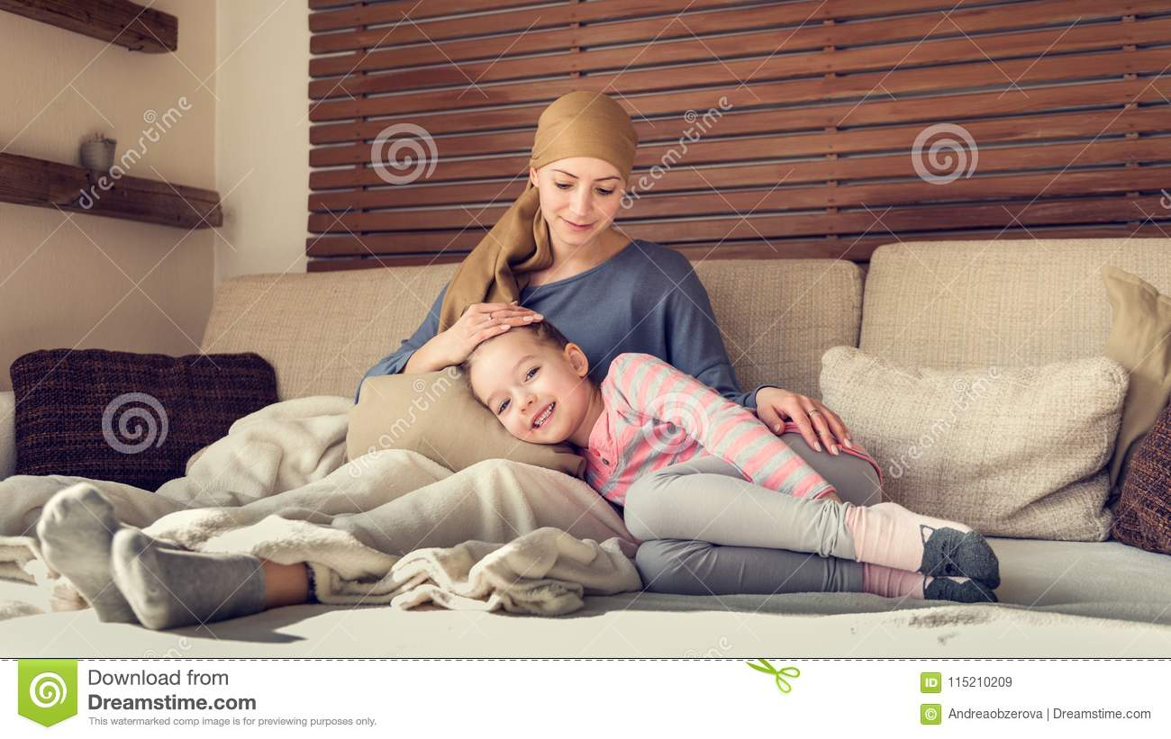 Young adult female cancer patient spending time with her daughter at home, relaxing. Cancer and family support concept.