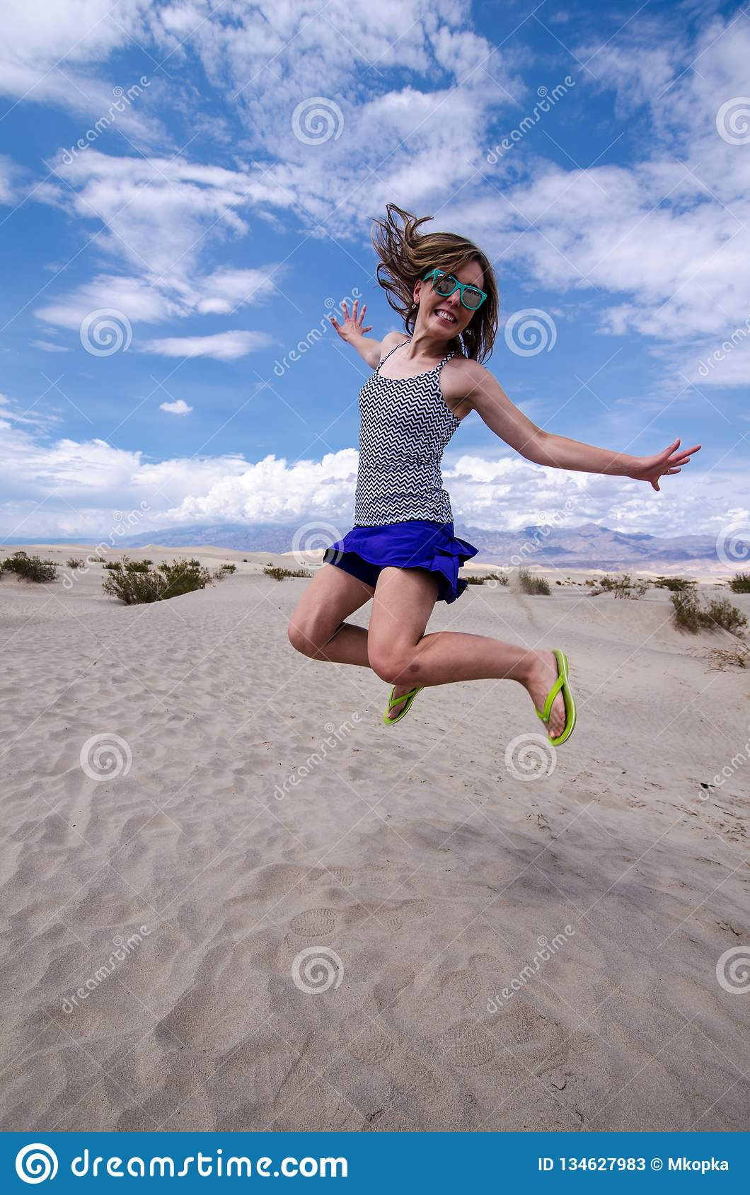 Young adult female woman jumps in the Mesquite Sand Dunes in Death Valley National Park in California