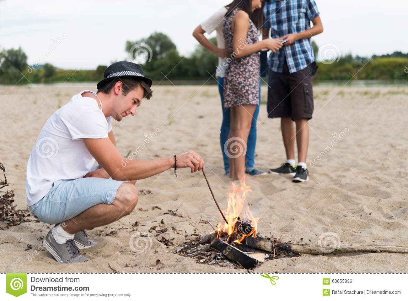 Young Adult Friends Hanging Around At Bonfire On Sandy ...