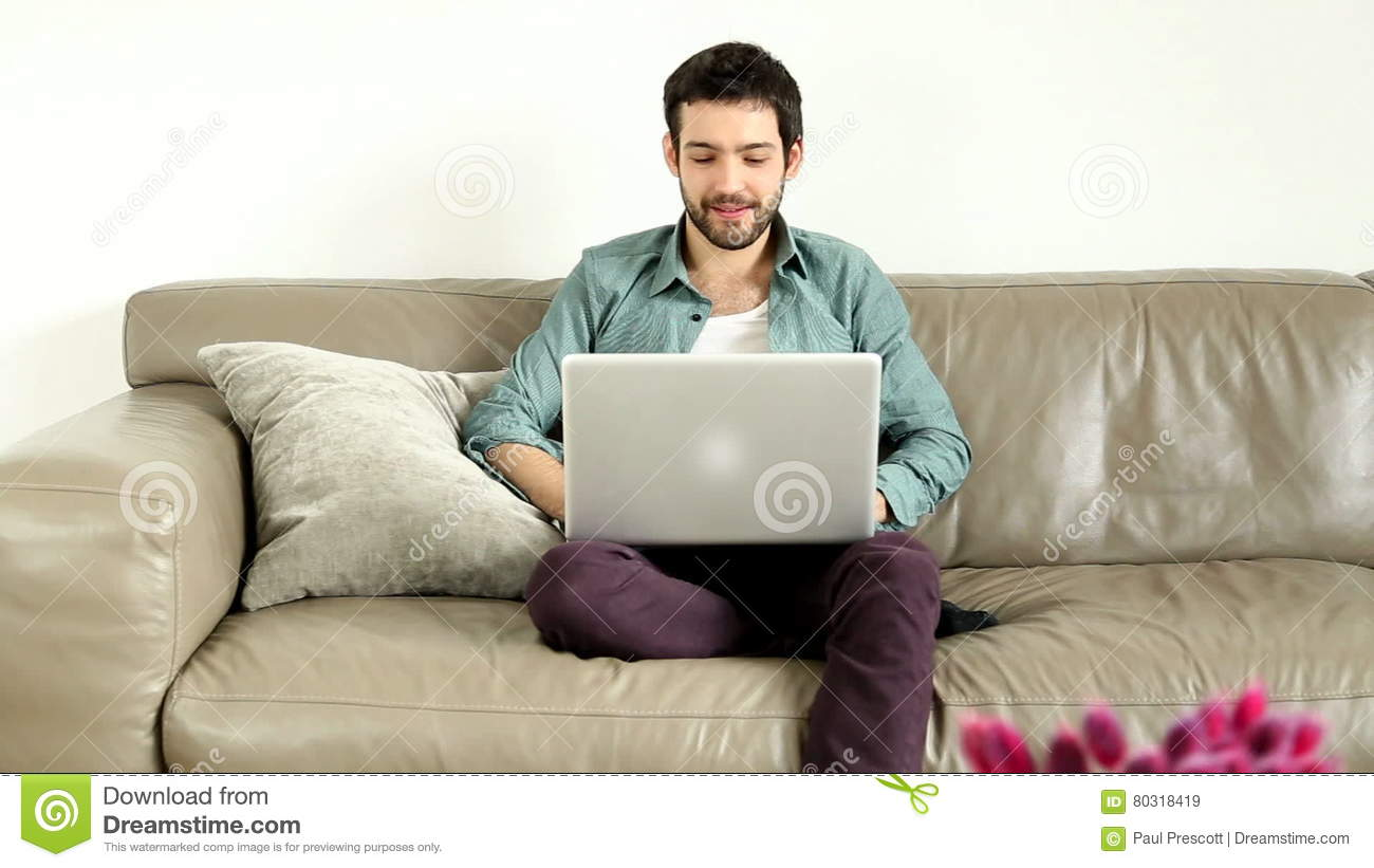 Young Adult Man Sitting On Couch In Living Room And Having ...