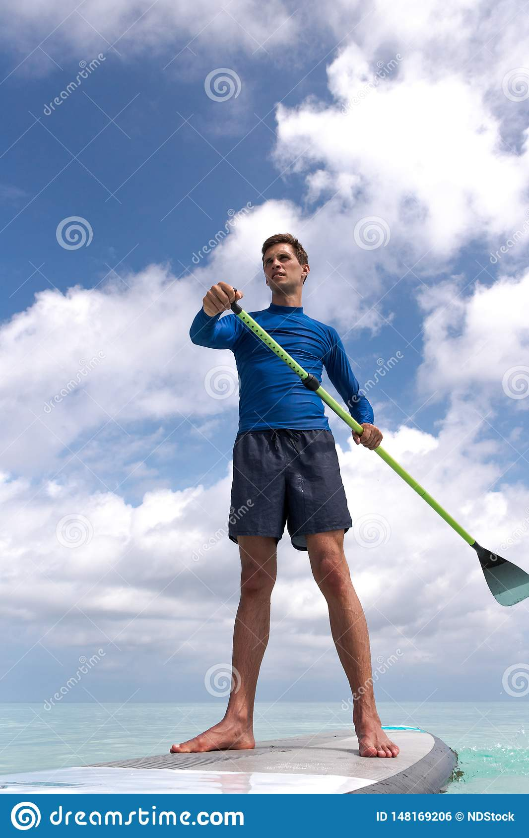 Young Adult Man with stand up paddle in clear blue water