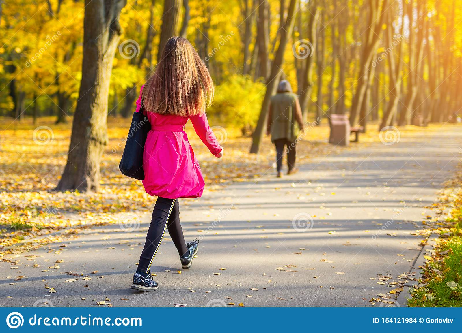 Young adult woman in bright casual coat walking along beautiful golden colored autumn park alley. Happy attractive sporty girl in