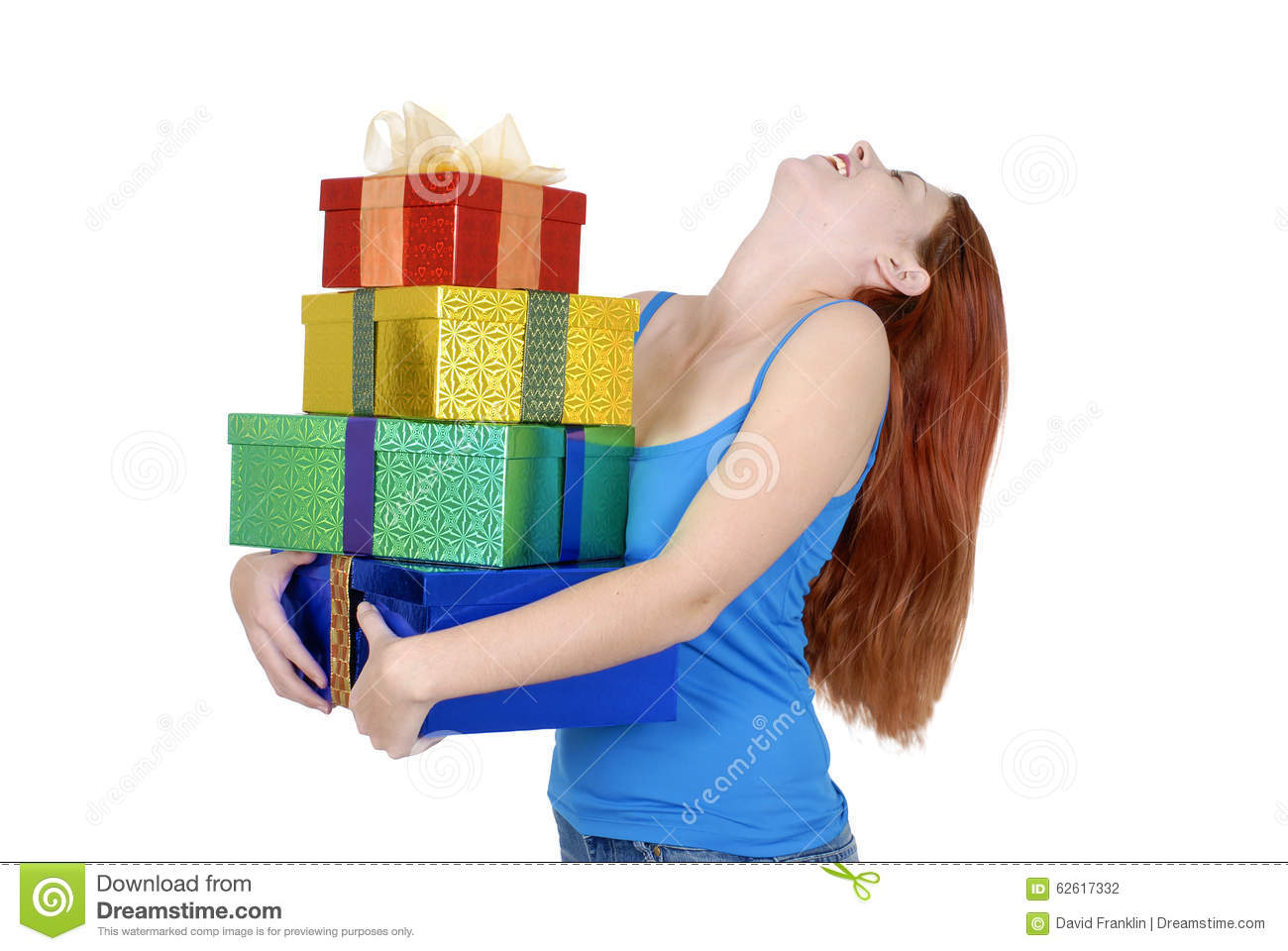 Young adult woman in casual clothes holding or carrying small pile of Christmas or birthday presents