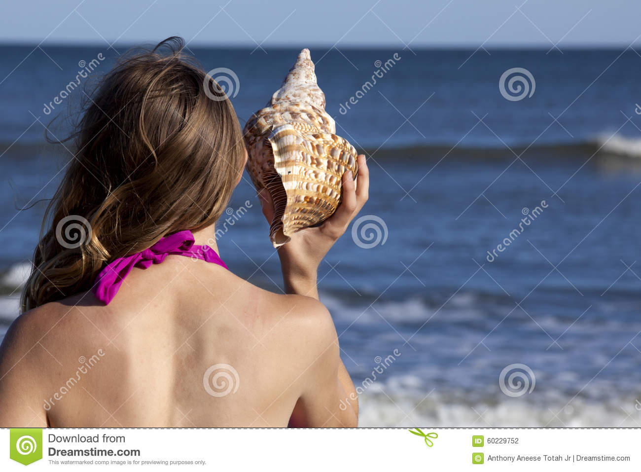 Young adult woman holding a triton seashell